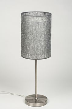 aRTIKEL 30610 Sfeervolle tafellamp met een fraaie cilindervormige kap. Het armatuur is uitgevoerd in staal. De cilindervormige kap bestaat uit twee gedeeltes; een binnen- en buitenkap welke in elkaar vallen.  http://www.rietveldlicht.nl/artikel/tafellamp-30610-modern-kunststof-staal_-_rvs-stof-wit-zilver(grijs)-rond