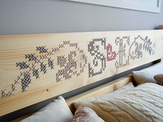 An amazing custom headboard has an embroidery detail.