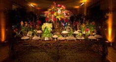 Para dar vivacidade aos espaços, tanto a mesa de doces quanto as dos lounges foram enfeitadas com peças altas ferro, ou vasos menores de barro ou de vidro, onde um mix de flores cor de rosa, amarelas, vermelhas e roxas foram dispostas de forma displicente.