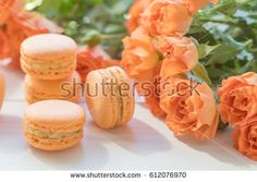 Orange mango or citrus macaroons and orange fresh little roses on light wooden background. Coloring and processing photo with light vintage style. Toned. Shallow depth of field.