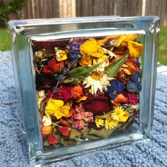 Cool way to save dried wedding flowers - glass block contains flowers from proposal bouquet, bride's bouquet, wedding reception tabletop dried flowers and centerpiece roses, and honeymoon bouquet!