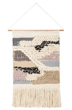 Enhance the cozy vibe of any space with a woven, fringe-trimmed wall hanging.