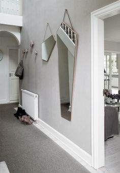Collage of mirrors in abnormal shapes creates a light and playful look in the entryway.