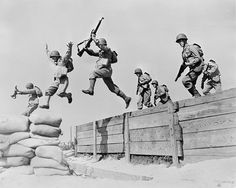 World War II, original caption A hard-running leap takes these artillerymen over one of the obstacles on the course at the anti-aircraft training center. Here we see the different phases of the jump; one man has just landed on the sandbags; two are in the air; and another man is gathering himself for the spring across', Camp Edwards, Massachusetts, 1942.