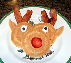 Awesome breakfast by elf on the shelf - - pancake Rudolph with strawberry red nose, bacon antlers, whipped cream and blueberry eyes.