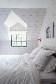 A peaceful and calming white bedroom with patterned wallpaper and black-and-white photo above bed: