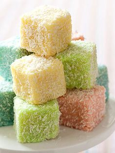 Coconut Squares--Traditional Australian finger cakes, known as Lamingtons. Trim Yellow cake into squares, spoon food coloring tinted lemon sugar glaze over squares, press coconut into sides, cool and Eat! Just Desserts, Delicious Desserts, Yummy Food, Healthy Desserts, Sweet Recipes, Cake Recipes, Dessert Recipes, Mini Cakes, Cupcake Cakes