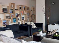 Os nichos da estante modular variam de tamanho. A madeira compõe o ambiente com estilo moderno (Foto: Maíra Acayaba/ Editora Globo)