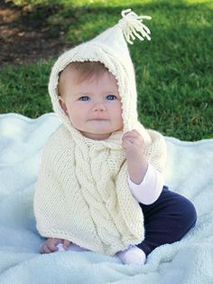 Knitting pattern for Teeny Poncho with hood and cable detail. Teeny Poncho  Sizes 6/9 (12/18, 24, 36/48) month. Annie's affiliate link