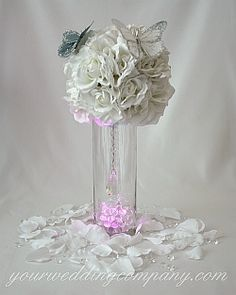 Cylinder vase centerpiece made with silk roses, glittered butterflies, rose petals, diamond confetti, an LED light & hanging crystal. http://www.yourweddingcompany.com
