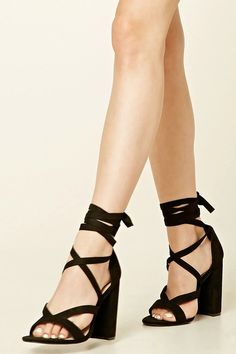 A pair of faux suede heels featuring a strappy design, open toe, self-tie ankle strap, and a chunky heel.