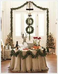 holiday style with greens and burlap and tiny white lights...garlanding the table.