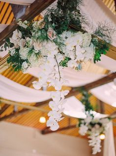 Hanging Reception flowers adorned an oversized frame in a small space.  Created by Akiko Floral Artistry.  Photo Credit:  Milton Photography.  #phalaenopsis #orchids #blush #gold #blushandgold #ivory #tulips #roses #peonies #hydrangea #wedding #flowers #hanging #reception