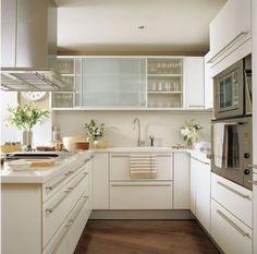 As portas de vidro do armário contribuem com a beleza e o charme dessa cozinha linda!