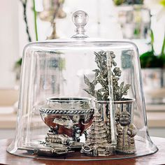 Call special attention to your favorite decorations this holiday season. Collect small figures and ornaments of the same color family and place under a glass cloche. Group individual items as a collection to make your display stand out. Budget project price: $6  /