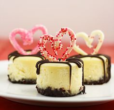 Valentine's Day MIni Cheesecakes~ this yummy dessert has a Nutella crust and a chocolate stuffed raspberry inside each cheesecake mini and it's topped off with a fun chocolate heart with sprinkles.