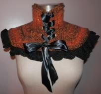 This is a stunning hand knitted neck warmer, firey orange with brown and gold accents and black ruffle. Beautifully laced with black satin ribbon finished with a large bow. Can be worn with any coat or jacket as well as over a sweater for a perfec... $35.00