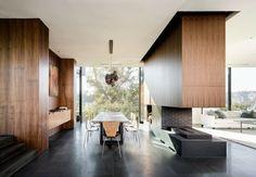 maison de verre et de béton avec salle à manger moderne, avec cheminée, meubles élégants et vue magnifique