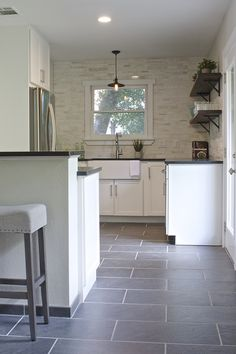 """We removed the pantry and moved the water heater to the garage to open up the space. The range with a downdraft was moved to the peninsula to create more counter space. A 33"""" wide and counter depth refrigerator fits perfectly into the bright cabinetry!"""