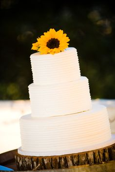 sunflowers on simple wedding cake with wood slab cake stand for rustic wedding #sunflowers #rusticwedding
