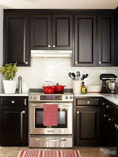 White subway tile meets black mosaic tile accents in this high-contrast backsplash. Stainless-steel appliances add gleam to the monochromatic palette, which is accented with pops of red./