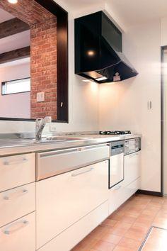 清潔感ある白のキッチンと掃除のしやすいレンガ色のクッションフロア。