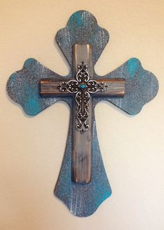 "Medium wooden, triple layer, wall cross. Painted with a textured grey spray paint and then distressed with white and turquoise acrylic paint. The second cross is a distressed, aged wooden cross which is then topped with a small ornate silver cross featuring a turquoise stone in the center. Dimensions are approximately 11"" x 15"". Each cross is handmade with love and truly one of a kind."