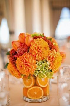 23 arranjos de flores para deixar qualquer ambiente mais especial: 6- Arranjo com frutas. Frutas inteiras ou em cortadas rodelas auxiliam na fixação das flores dentro do recipiente e conferem um estilo tropical à combinação. Essa é uma excelente alternativa para compor a ornamentação de eventos em dias quentes.