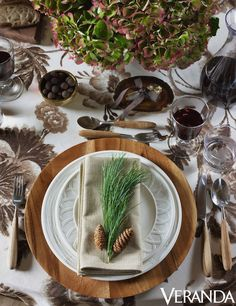 Aerin favors round tables for entertaining and a palette of one/two colors carried throughout. Here her Hither fabric for Lee Jofa sets a neutral patterned background for her woodland chic wooden chargers and plates for Lenox, recalling the charm of winter white fisherman knit sweaters. At each place rests a gift of an elegant wine stopper Aerin designed, a gesture borrowed from her grandmother who always included a little something for each guest at her table.