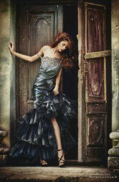 Rapariga ruiva com vestido cinzento à frente de uma porta aberta