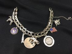 VINTAGE 1950S STERLING SILVER CHARM BRACELET WITH 8 CHARMS INCLUDING A DOG, ELEPHANT, ROCKET, JAVELINA, FLAG AND MORE. MEASURES 8 INCHES. GOOD CONDITION. TWO CHARMS UNMARKED. WEIGHS 45 GRAMS.