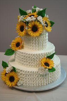 Three tier (white, chocolate, white) cake with gumpaste sunflowers, white roses, stefanotis and babies breath.  Petal affect icing.