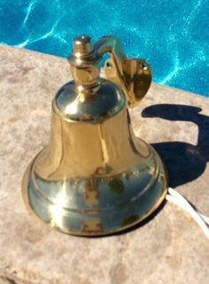 Beautiful large brass mounted dinner bell with rope pull. Solid heavy brass captains bell in very good vintage condition! Minimal wear to lacquered brass finish. Ready for home or outdoors! Goes with so many home decors from nautical to mid century. Has a strong distinct ring! Has number 8 engraved on inside ⚓️Will ship insured! Measures 7 height bell x 6.25 diameter, 7.5 depth from wall when mounted Thanks for shopping YellowHouseDecor! Several brass nautical items sold in shop