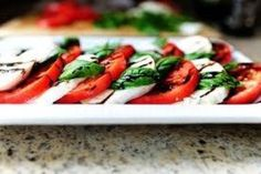 Slice each tomato from top to bottom into 1cm thick slices. Place on a serving plate and top with the mozzarella and basil leaves. Sprinkle with salt and pepper. Drizzle with oil and vinegar and serve.
