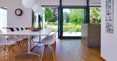 Baufritz Bauhaus Russell – Große bodentiefe Fenster lassen wärmende Sonnenstrahlen in den kälteren Jahreszeiten hinein und fungieren als zusätzliche Heizquelle im Haus.