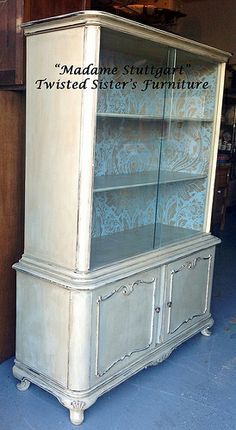 """Madame Stuttgart ""Re-Birth Date 11//6/13.This beautiful vintage china cabinet was refinished by Twisted Sister's Furniture w/Annie Sloan chalk paint in Country Grey w/dark & clear wax. It has a lovely blue/green damask wallpaper on the inside. Visit http://www.twistedsistersfurniture.com for more info."