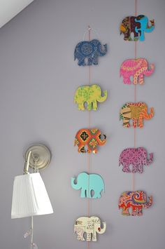 DIY Elephant (or anything u want!!) hanging cutouts. Find a stencil online and trace it onto different colored scrapbook paper. Then tape, glue, or staple onto a string. Ta-da!