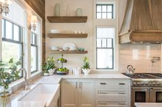 An oak French kitchen hood, flanked by windows, stands over a gray striped…