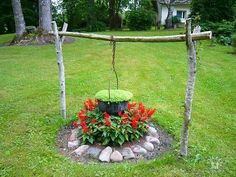 old cauldron used as a planter and made to look as if over a fire and has green brew in it!