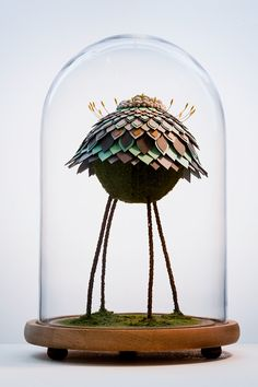 """In her ongoing sculptural series titled """"The Marriage,"""" Malaysian artist Noreen Loh Hui Miun merges elements from real and fictional plantlife to create entirely new species. The fragile works begin with dried plant components like branches and moss to which she adds cut laminate petals reminiscent"""