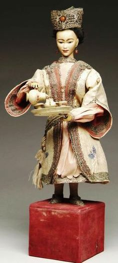 dolls, France, A French Automaton of an Asian Woman Pouring Tea. Amber tinted bisque flange Jumeau head with closed mouth and inset brown glass almond shaped eyes, wearing costume of embroidered silk with metallic lace trim. When wound the woman raises and lowers her head, pours tea from teapot in right hand into a cup located on a tray in right hand. Left hand also extends to the far left and she also raises the teapot to the level of her head. She is wearing her original black mohair wig…