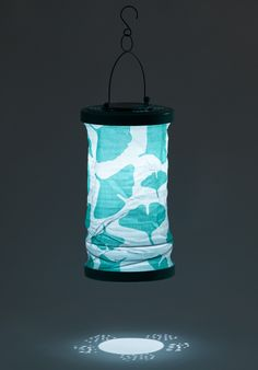 The Soji™ Ginkgo solar lantern is bold and bright by night! With a hand-punched metal top and bottom, and a custom designed Ginkgo printed canvas, light shines throughout when illuminated at night. Canvas fabric and solar lighting combine in a festive turquoise Ginkgo print to make your garden glow!
