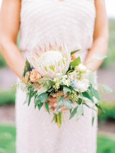 Protea and greenery wedding bouquet: http://www.stylemepretty.com/north-carolina-weddings/2017/03/15/from-a-beach-proposal-to-a-bohemian-garden-seaside-wedding/ Photography: Love by Serena - http://lovebyserena.com/ Assistance: Faith Teasley - http://www.faithteasley.com/