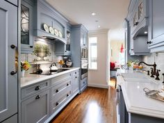 Influenced by an English cottage design, this blue traditional kitchen emphasizes the quaint and soft details of that style.