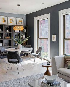 salle à manger moderne et élégante avec une peinture murale grise et aménagée avec des chaises grises et une table tulipe blanche