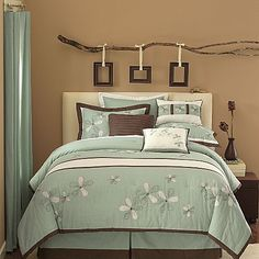 Some of the details in this room have a sort of country whimsy to them (the flowers on the bedding, the really cool use of the branch, etc.) but the modern colour palette really gives it a unique style! Love the mixing of the tans, browns, and blues. #bedroom