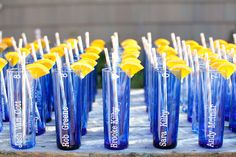 They stumbled upon these blue glasses found at Ikea and had them customized with the guests names and topped off with orange slices and orange straws for place settings and take home gifts