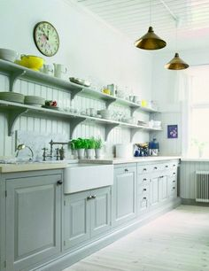 grey kitchen cabinets and shelves, ivory countertops, farmhouse sink
