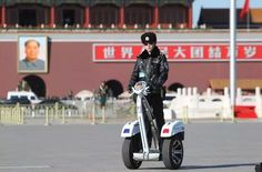 Policemen ride two-wheel electronic vehicles at Tiananmen Square ahead of a plenary session of the Chinese People's Political Consultative Conference in Beijing's Great Hall of the People on Tuesday.