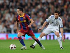 Xabi Alonso Photos - Xavi Hernandez (L) of Barcelona controls the ball besides Xabi Alonso of Real Madrid during the la Liga match between Real Madrid and Barcelona at Estadio Santiago Bernabeu on April 16, 2011 in Madrid, Spain. - Real Madrid v Barcelona - La Liga
